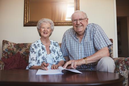 Portret van een glimlachend gepensioneerd paar dat over documenten kijkt. Hogere Kaukasische man en vrouwenzitting op bank bij oude dag naar huis en ondertekenend wat administratie. Stockfoto