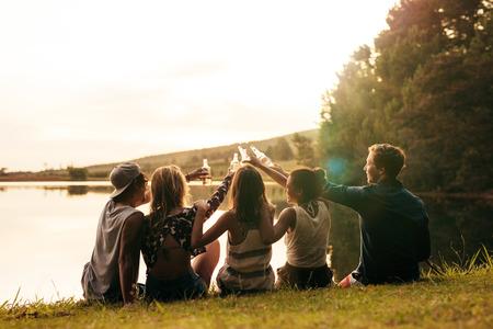 Grupo de jóvenes sentados en una fila en un lago con las cervezas. Jóvenes amigos tostado y celebrando con cervezas en el lago en un día soleado.