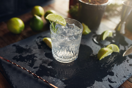 Close up of freshly made gin and tonic drink with lemon slices and spoon on a black board.