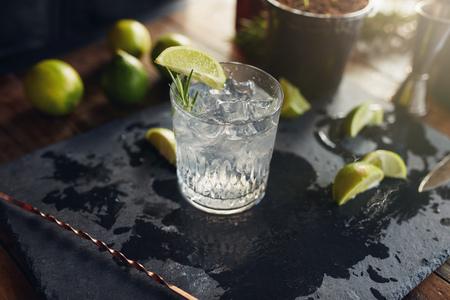 Close-up van vers bereide gin-tonic drinken met schijfjes citroen en lepel op een zwarte bord. Stockfoto