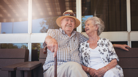 break: Portrait of handsome senior man sitting with his wife on a bench outside their house. Retired couple taking a break and relaxing outside their home.