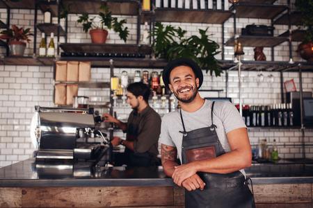 커피 숍 작업자 카운터에 서있는 카메라에 미소. 백그라운드에서 작업하는 웨이터와 카페 카운터에 기울고 앞치마와 모자에 행복 한 젊은 남자가있다.
