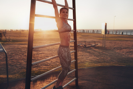 wall bars: Portrait of happy young female exercising on wall bars outdoors during sunset. Fitness woman doing stretching and looking at camera. Stock Photo