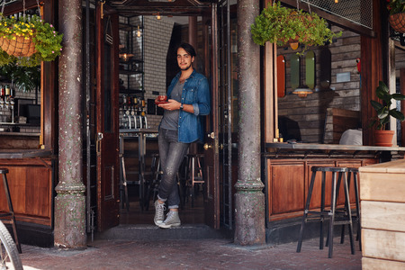 Full length portrait of relaxed young male standing at the entrance of a cafe and having coffee. Stylish young man at a cafe entrance door. Stock Photo