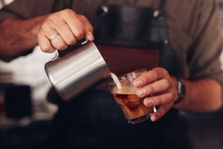 cropped shot: Cropped shot of coffee being prepared by a barista. Focus on hands holding cup of coffee and milk jar.