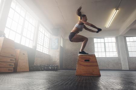Seitenansicht Bild der jungen Frau passen eine Box Sprung Übung. Muskulöse Frau, die ein Feld hocken am Kreuz fit Fitness-Studio machen