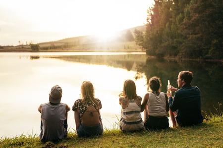 grupo de personas: imagen de visión trasera de jóvenes sentados en una fila por un lago y mirando la puesta del sol. Grupo de amigos que se sientan por un lago y relajante.