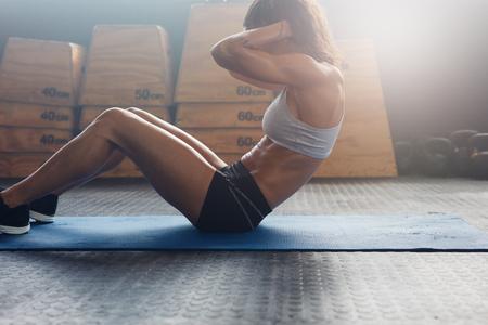 ejercicio: tiro bajo techo de fitness femenino que trabaja en el gimnasio. mujer haciendo ejercicios de estómago jóvenes musculosos.