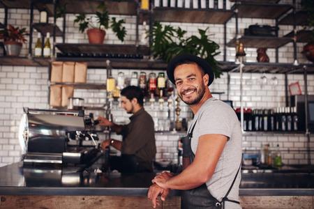 Portret van gelukkige jonge mannelijke koffiewinkel eigenaar staan met barista werken achter de balie drinken maken.