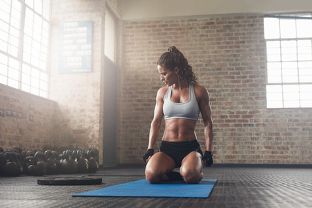 Indoor shot of fitness young woman sitting on yoga mat at gym. Muscular young female athlete taking a break from her workout..