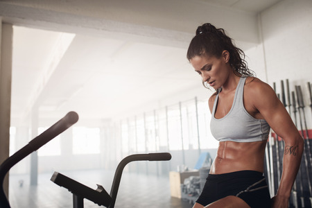 Fitness woman sitting on a bicycle in gym.  Fit young female exercising on gym bike.