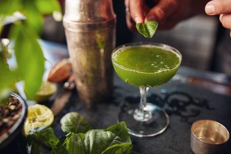 basils: Close up shot of bartender garnishing fresh green cocktail with a basil leaf. Barman preparing basil smash cocktail. Stock Photo