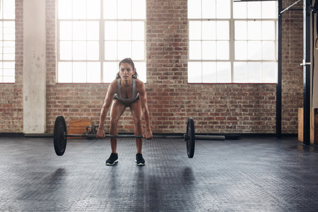 snatch: Fit young female holding a barbell in her hands. Crossfit woman lifting heavy weights in gym.