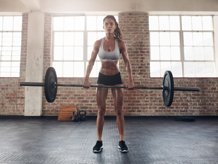 heavy lifting: Full length image of tough young woman exercising with barbell. Determined female athlete lifting heavy weights.