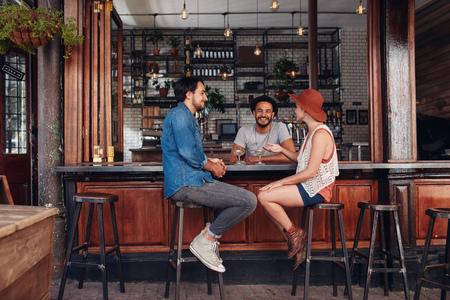カフェに座って、話を若い人たちのグループです。若い男性と女性がカフェのテーブルでの会議します。