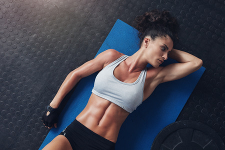 laying abs exercise: Top view of fitness woman resting on exercise mat after her physical training session. Young female in sportswear lying on mat in gym and looking away. Stock Photo