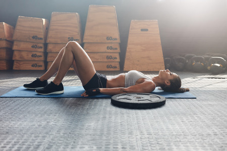 lying on side: Side view shot of fitness woman resting on exercise mat with a heavy weight plate on floor. Female athlete lying on her back after a gym workout Stock Photo