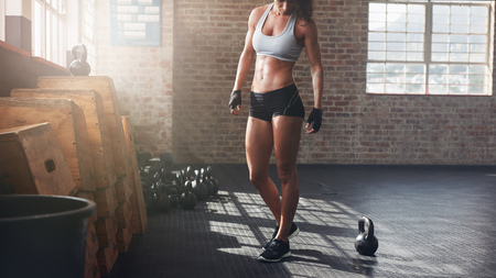 Cropped shot of muscular woman standing in crossfit gym. Fitness female model in sportswear with kettle bell on floor.
