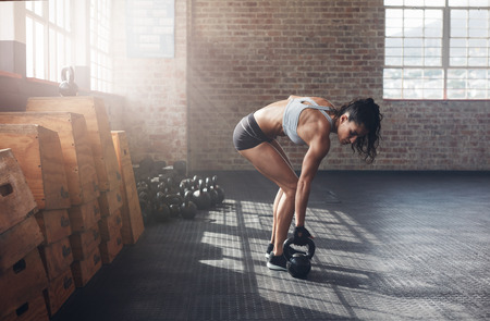Full length shot of fitness woman doing crossfit exercising with kettle bell. Determined female model about to start her fitness regime at the crossfit gym.