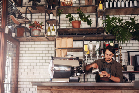Indoor shot of young male barista making a cup of coffee while standing behind cafe counter. Young man pouring milk into a cup of coffee. Stockfoto