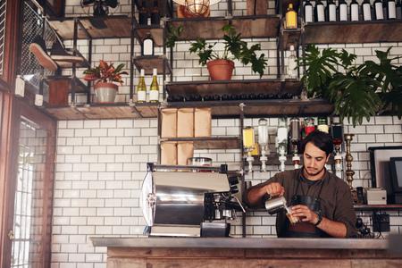 tiro bajo techo de barista varón joven de tomar una taza de café mientras está de pie detrás del mostrador del café. joven verter la leche en una taza de café.