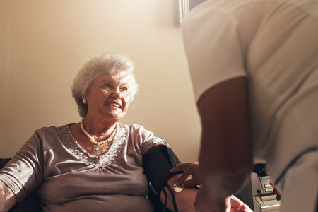 elderly woman: Senior woman sitting on a chair at home with female caregiver checking her blood pressure. Elderly woman getting routine check from a female doctor.