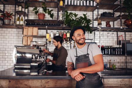 Portret van cafe-eigenaar die een hoed en schort draagt die bij de balie staat en wegkijkt. Barista werkt in de achtergrond achter de balie om drankjes te maken.