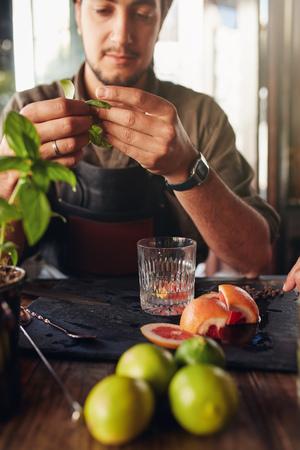 barmen: Cocktail preparation ingredients on table with bartender holding basil leaves.
