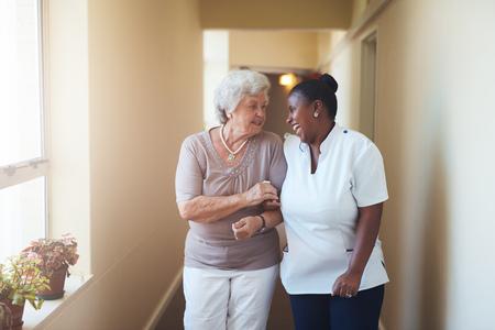 Portret van happy vrouwelijke zorgverlener en senior vrouw lopen samen thuis. Professionele mantelzorger de zorg voor bejaarde vrouw.