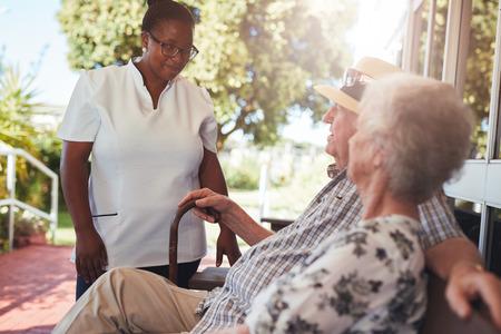 maison Femme soignant soignant couple de personnes âgées de détente sur un banc à l'extérieur de leur maison de retraite.