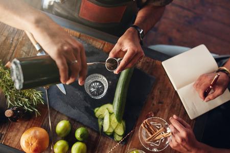 Dwóch barmanów eksperymentowania z tworzenia napojów koktajl. Widok z góry człowiek wylewanie mieszanki na jigger przygotować koktajl i kolejny zdejmując notatki. Zdjęcie Seryjne