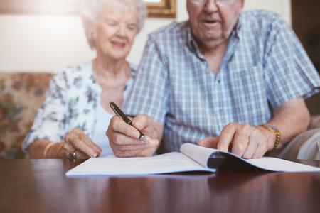 高級夫婦簽署將文件。老年白人男人和女人坐在家中,並簽署一些文件,注重手。