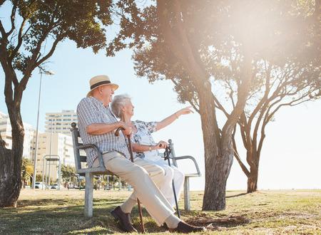 彼女の夫に何か面白いものを見せて女性と公園のベンチに座っている年配のカップルの屋外撮影。引退したカップルの休憩を取って、ベンチでリラ