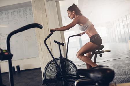 Fit молодая женщина, используя велотренажер в тренажерном зале. Фитнес женщина с помощью воздуха велосипед для кардио тренировки в CrossFit тренажерном зале. Фото со стока