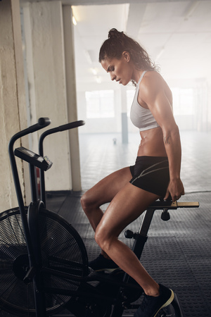 intense: Muscular young woman working out on the exercise bike at the gym, intense cardio workout.