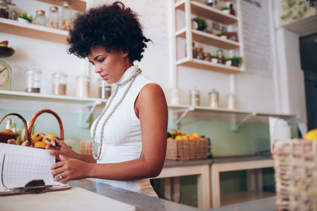 woman behind: Indoor shot of young african woman doing accounts. Female juice bar owner standing behind the counter and looking at some papers. Stock Photo