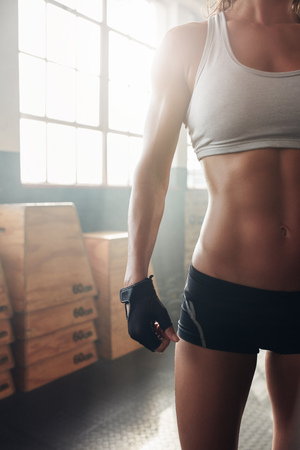 cropped shot: Cropped shot of fit womans torso. Female with perfect abdomen muscles standing at the gym.