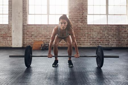 체중 바 여성 수행 드리프트 운동. 자신감이 젊은 여성 무게 체육관에서 운동을 리프팅을하고.
