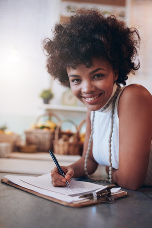 behind: Portrait of smiling young woman working in a juice bar and writing notes. African female standing behind the counter looking at camera and smiling. Stock Photo