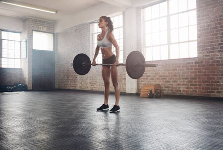Fitness woman preparing to practice deadlift with heavy weights in gym. Female doing heavy weight lifting work out in health club. Stock Photo