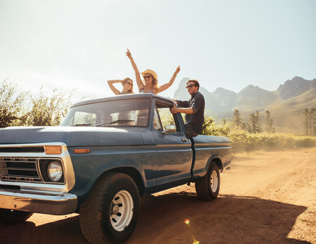 pick up truck: Group of people at the back of a pick up truck having fun. Young men and women enjoying on a road trip in countryside on a sunny day.