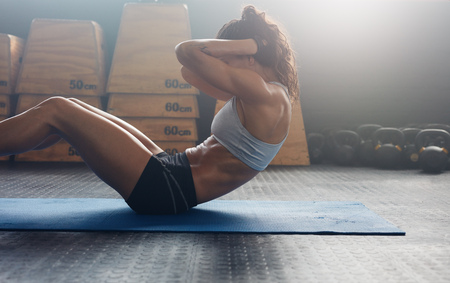 situps: Sporty young female athlete on yoga mat doing situps in gym. Fitness woman doing abs crunches.