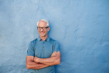 Ritratto di un uomo felice maturo in piedi con le braccia incrociate contro un muro blu. Maschio caucasico con gli occhiali guardando lontano e sorridente.