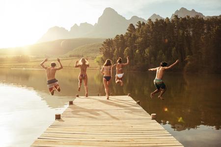 Группа молодых людей, прыжки в воду с причала. Группа друзей прыгает от пирса в озеро в солнечный день.