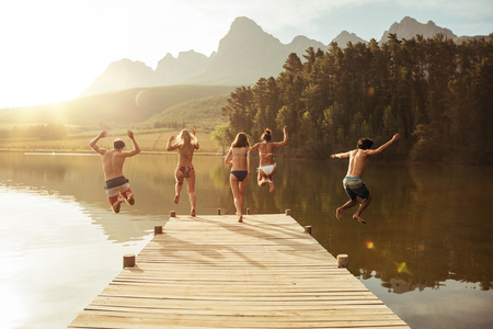 Grupa młodych ludzi skaczących do wody z pomostu. Grupa przyjaciół skacząc z molo na jeziorze w słoneczny dzień. Zdjęcie Seryjne