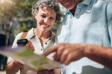 personas reunidas: pareja de mediana edad mirando el mapa de la ciudad. Mujer madura feliz con su marido en unas vacaciones de verano. Foto de archivo