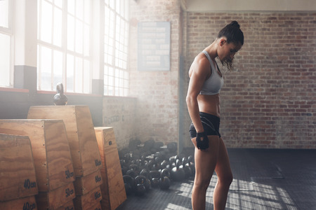 muscular body: Side view shot of muscular young female athlete in sportswear standing at the gym. Fitness woman preparing herself for the intense workout at gym. Stock Photo