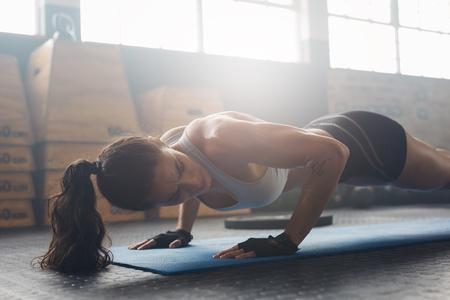 Plan de la jeune femme faisant push-ups dans le gymnase. athlète féminine Forte faire des pompes sur le tapis d'exercice à la salle de gym. Femme exerçant sur le tapis de fitness au gymnase. Banque d'images