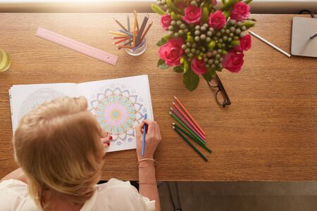stress woman: Top view of woman coloring floral designs with color pencils for relaxation at home. Anti stress adult coloring book. Stock Photo