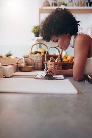 woman behind: Image of young african woman calculating expenses on a writing pad. Female juice bar owner accounting at the counter. Woman writing notes while standing behind cafe counter.